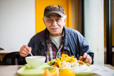 Un résident de la Maison d'Accueil des Petits Riens profite d'un repas chaud équilibré.